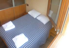 Dormitorio doble con colcha de cuadros