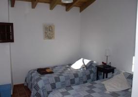 Dormitorio matrimonial con colcha blanca en casa rural