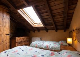Dormitorio abuhardillado con las camas individuales
