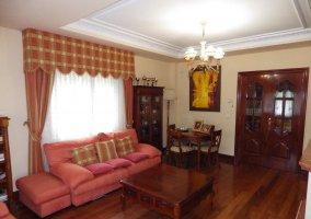 Sala de estar con sillones en naranja frente a la chimenea