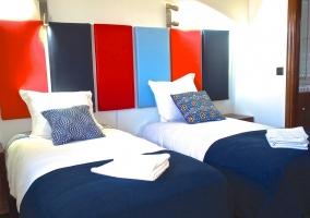 Dormitorio doble con detalles azules y rojos