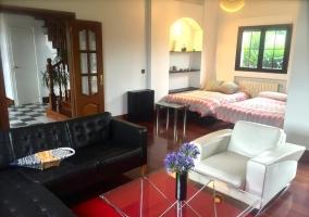 Sala de estar con sillones en color negro y mesa de cristal