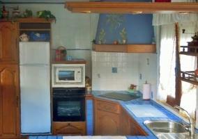 Cocina de la casa en color azul y ventana.JPG