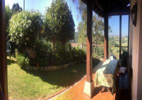 Vistas del porche con mesa y jardines