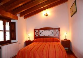 Dormitorio de matrimonio abuhardillado con colcha naranja