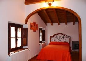 Dormitorio con cama de matrimonio y techos de madera