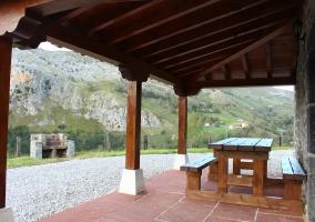 Vistas del porche de la casa con la barbacoa y el patio