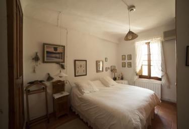 Dormitorio con cama de matrimonio y colchas en blanco