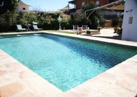 Acceso a la casa con fachada en blanco y piscina
