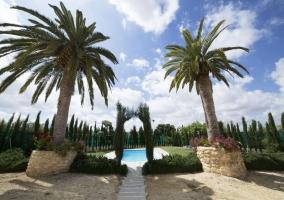 Acceso a la casa con la piscina y sus jardines