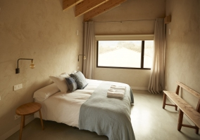 Dormitorio con cama de matrimonio y gran ventanal