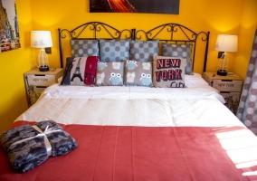 Dormitorio con cama de matrimonio y cabeceros de forja