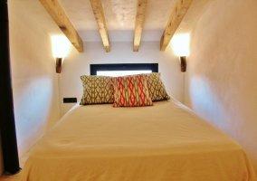 Dormitorio con cama amplia y vigas en madera