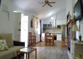 Sala de estar y cocina con mesa de madera