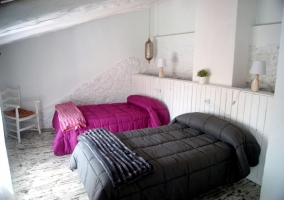 Bedroom with a couple of beds and colorful blankets