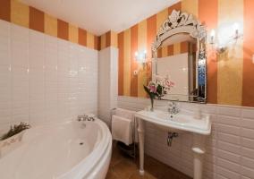 Dormitorio de matrimonio y aseo con espejo