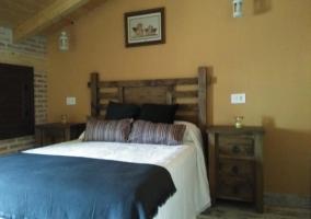 Dormitorio con cama de matrimonio y cabecero de madera