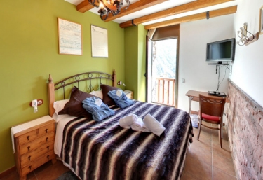 Dormitorio doble verde con cama de matrimonio amplia