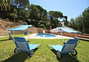Amplias vistas de la piscina con hamacas delante