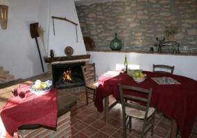 Cocina con chimenea y mesa de comedor al lado