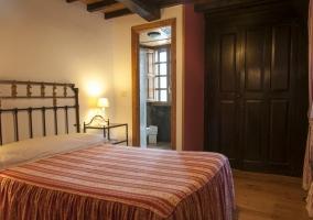 Dormitorio con su aseo y suelos de madera