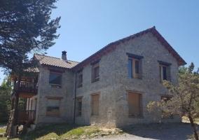 Acceso a la casa con fachada de piedra y detalles en madera