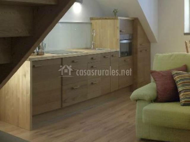 Salón cocina con sillón verde y encimera de madera