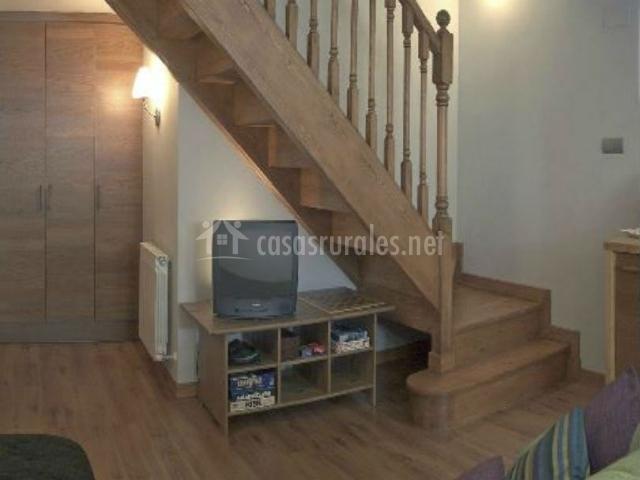 Salón con televisor y escaleras al primer piso