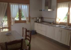Cocina con armarios en blanco y mesa