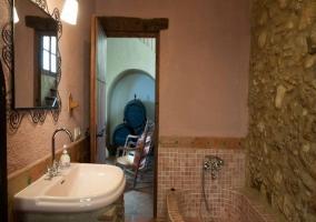 Aseo con paredes de piedra y lavabo