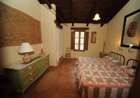 Dormitorio con dos camas y mueble verde