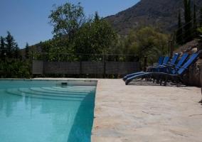 Fuente en la piscina con tumbonas