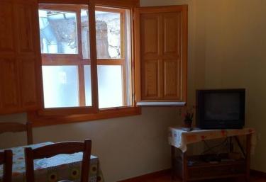 Sala de estar con tele de plasma y mesa de madera