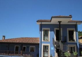 Acceso amplio con fachada en azul y ventanas