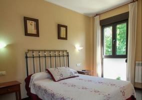 Dormitorio de matrimonio con colcha en blanco y burdeos