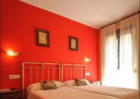 Dormitorio doble con paredes rojas y colchas