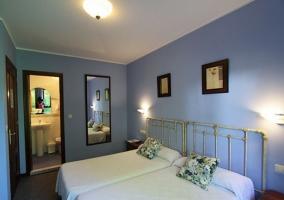 Dormitorio doble en color azul con colchas en blanco