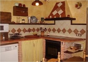 Cocina con ladrillo y azulejos de la casa rural