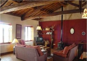 Zona de estar con televisión y chimenea en la casa rural