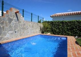 Amplia piscina de la casa con hamacas al lado