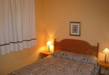 Dormitorio de matrimonio con mesilla y pared amarilla