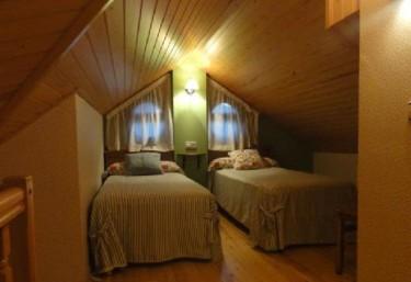 Dormitorio con un par de camas y suelos de madera