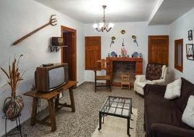 Sala de estar con la chimenea y la mesa de madera con sillas