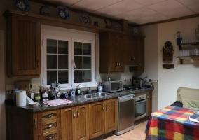 Cocina y sala de estar con chimenea haciendo esquina