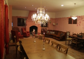 Salón-comedor con sofás, chimenea y mesas