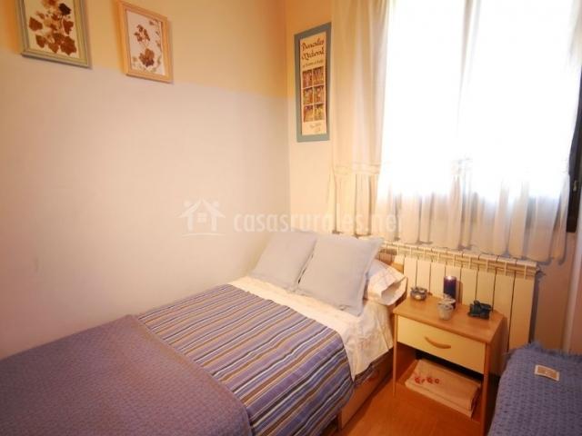 Dormitorio con ventanal y cuadros decorativos