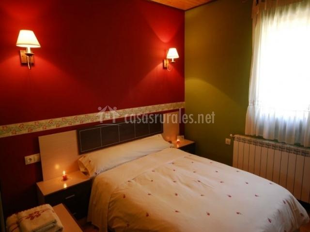 Dormitorio de matrimonio con pared en tonos rojos
