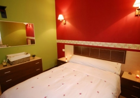 Dormitorio de matrimonio con pared en tonos rojos y cómoda