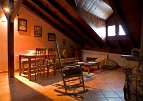 Sala de estar abuhardillada y la chimenea junto a la mecedora