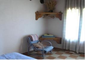 Dormitorio con cama doble y detalle decorativo en la pared de la casa rural